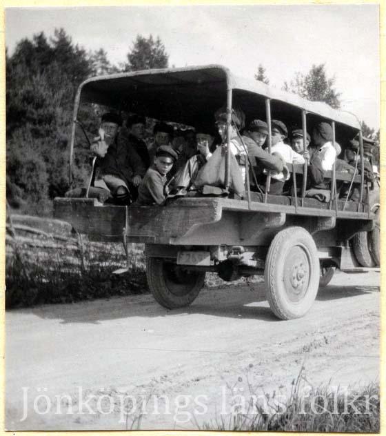 Foto på ett tjugotal pojkar som trängs på ett lastbilsflak med tak, men med öppna sidor.