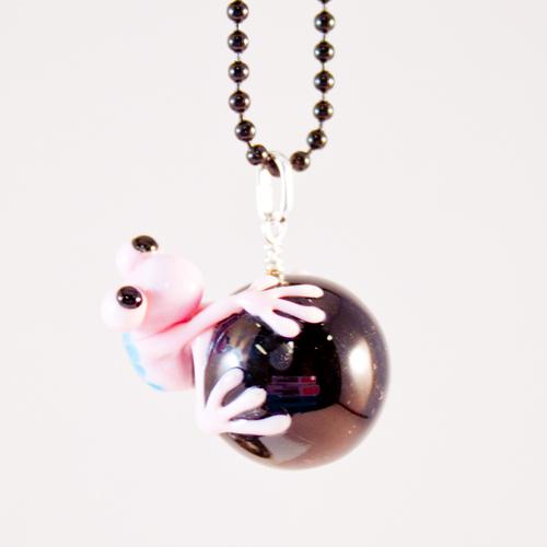 Groda rosa på svart kula framifrån