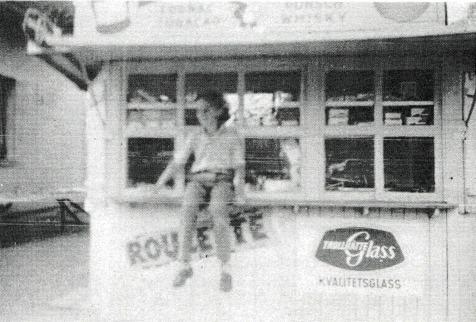 """A. 36 (5) Endast digital bild! Edith berättar att de vid inflyttningen bestämt sig för att fortsätta driva caférörelsen och att utöka kioskverksam- heten och sökte därför tillstånd att bygga ut huset mot öster - mot det gamla församlingshemmet. Närheten till kyrkan gjorde verksamheten lönsam och Edith minns att det hon en gång räknade till sammanlagt 21 bussar parkerade på den stora planen västerut. """"Den dagen var vi tre personer som sålde och serverade. Själv tog hon hand om Café´t"""" - minns Edith. I Caféet fanns 20 sittplatser. Makarna Edtih och Erik Pettersson hade själva fyra barn som kunde hjälpa till, Eddie, Gullan, Majvor och Hasse, och naturligtvis deras kamrater. Café-delen utnyttjades också av årskurs 1-2 i småskolan (Församlinghemmet) och årskurs 5-6 i Folkskolan som matbespisning. Edith iklädde sig rollen som mattant under många år. Maten, vanlig husmanskost som serverades eleverna, tillagades i Skara och kördes ut med taxi. En del dagar blev det trångt i matsalen och då fick eleverna använda hennes eget kök för att äta i. Matbespisningen pågick tills den nya skolan blev färdig i slutet på 1970-talet några år före den förödande branden 1979. (Bygger på en berättelse av Edith Pttersson för Eva Bozovic, Varnhem 1997 - publicerad i Varnhemsbygden 1998). Insatt av Kent Friman, 2014-02-24. Läs mer på www.saj-banan.se!"""