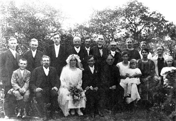 """A. 30 (2) Endast digital bild. Foto från bröllopet midsommarafton 1924 taget vid Hålltorps kvarn i trädgården. Vigsel förrättad av kyrkoherde von Südow i Varnhems kyrka.  Främre raden från vänster:  Erik Berglund,  – fosterson till August och Eugenia på Ivarstorp, blev med tiden präst i i Skåne i de sammanlagda församlingarna Everlöv – Bläntarp – Sövde. Han vigde senare Oskars och Annas son Bengt Jonsson och hans maka Inga-Lill. Han blev fosterson i Ivarstorp xxxx på grund av ensamstående moderns omöjlighet att klara situationen ekonomiskt i Stockholm och flyttade ut xxxx. Gick i skolan i Varnhem med Håkan Gabrielsson som lärare med gående skolväg från Ivarstorp till Varnhems skola. Formalia: Erik Runo Berglund född 1911 i Kungsholms församling, Stockholm död 1994 i Lund, prästvigd 1943, kyrkoherde i Sövde i Lunds stift, gift 1954 med Ella Oscaria född 1908 i Holm i Hallands län, död 1987 i Lund. Inga egna barn. Gustaf Linus Berg (Annas far) Anna född Berg och Oskar Jonsson (brudparet) Charlotta Berg (Annas mor) Ester Sköld född Jonsson (Oskars syster) gift Sköld i Stenstorp, med dottern Margareta i knät. Margareta gift Eriksson - bor i Mariestad (2013). Jenny Andersson (Oskars halvsyster) och Margit Granström, släkt med sömmerskorna Persson som lärde Anna till yrket  Bakre raden från vänster:  Viktor Andersson (Jennys make - kallades ofta """"Karl Johannas-Viktor"""" - bor vid tiden i torpet Gröngatan, Backa), Viktor spelade fiol och kallades också """"Spele-Viktor"""". Arvid Pettersson, Godsägare på Hålltorp,  född i Varnhem 1870 den 12/2 - på fotot i en ålder av 54 år  Hugo Sköld (Oskars systers Esters make), järnvägstjänsteman, Stenstorp Kjellander, Lundby Sven Pettersson, ägare till Redsvenstorp boendes i Smedsgården, Överbo Tekla Johansson, Vadet (en av syskonskaran i Vadet) August Johansson i Vadet (en av syskonskaran - som senare köpte Annelund, Ljungstorp) Elisabeth Johansson, Vadet (en av syskonskaran) Margit Persson, sömmerska syster med Hulda Persson, sömmerska - An"""