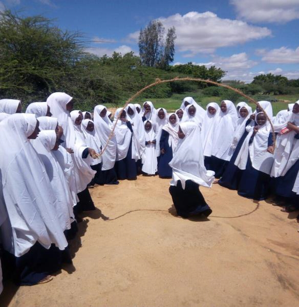 Girls playing with ropes at the school compound during break time.