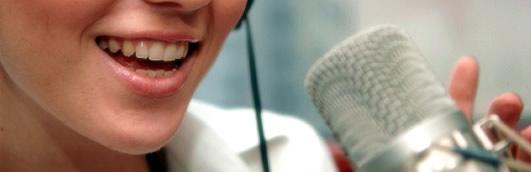 Syntolkning: Närbild på ett  ansikte med glad mun framför en mikrofon.