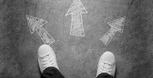 Två fötter som som står vid 3 pilar. Vet inte vilken väg de ska ta.