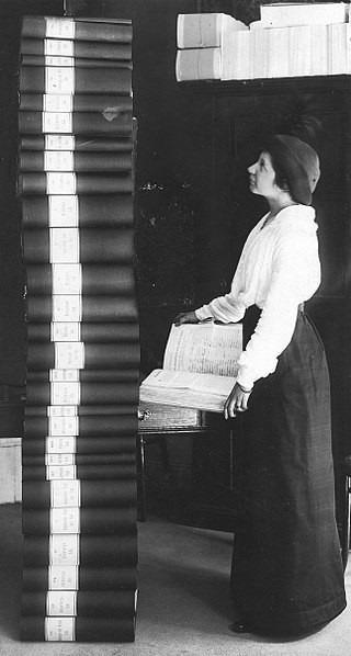 Författaren Elin Wägner framför de 30 banden med 351 454 underskrifter som behövdes för att få riksdagen att ta upp frågan om kvinnlig rösträtt.  Okänd fotograf / KvinnSam, Göteborgs universitetsbibliotek