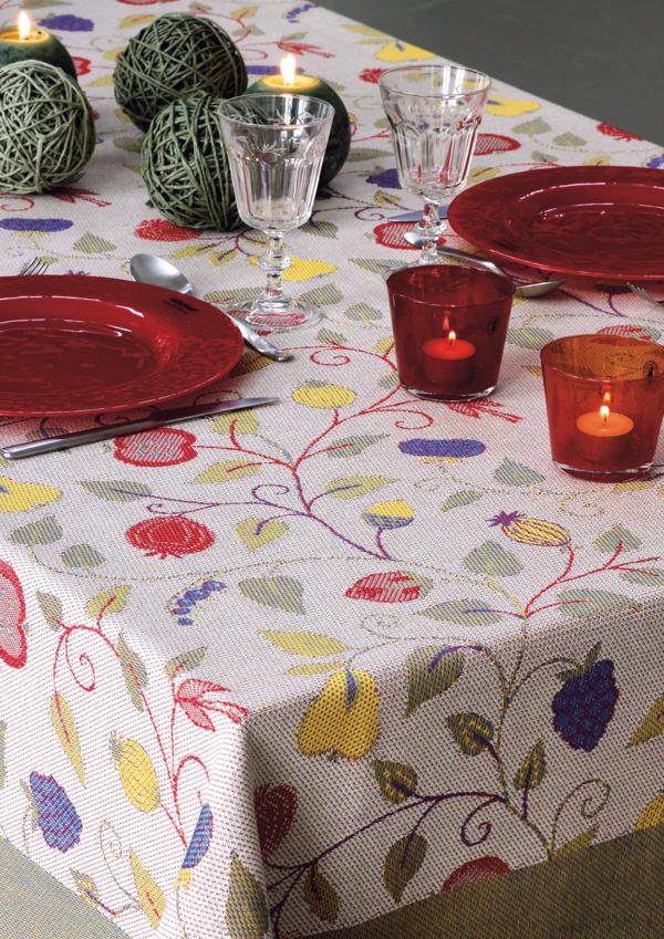 Bordsduk på ett bord med blad och blommor i flera färger. Rött porslin och  2 st röda ljuslyktor