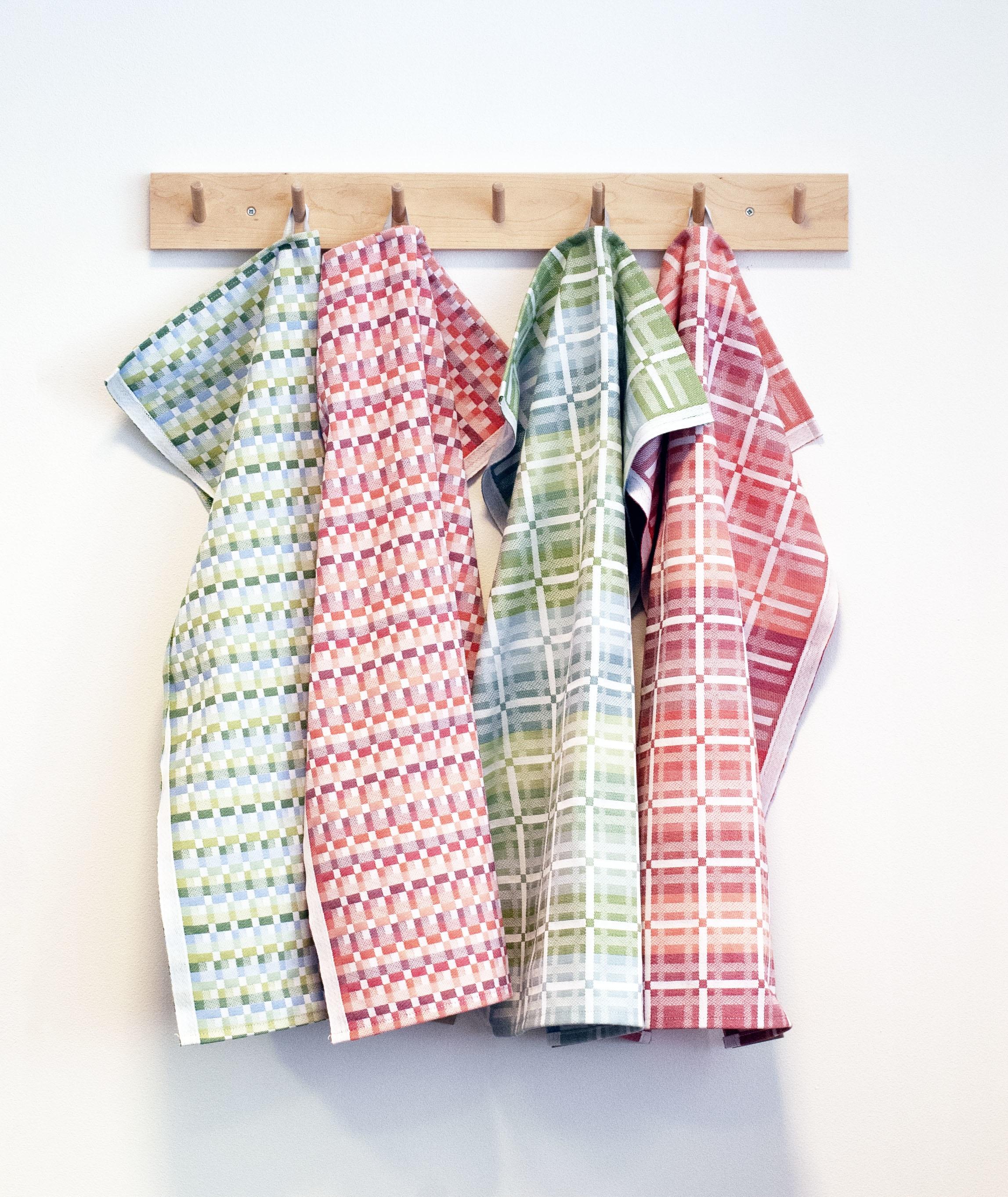 Fyra handdukar som hänger på en krokbräda