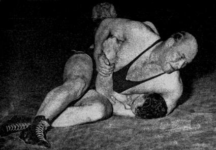 """En klassisk bild på en klassisk brottare - BoIS tungviktsankare Erik """"Falka-Erik"""" Johansson har motståndaren i en besvärlig situation. """"Falka-Erik"""" var under många år höjdpunkten på brottargalorna och han tävlingsbrottades ända tills han fyllde 49 år! """"Falka-Erik"""" var med i Hallandslaget i brottningsevenemanget i Varbergs Simstadion 1951, och fick då möta mästarbrottaren Bertil Antonsson i en sevärd match. Bertil förstärkte Kairos lag, som saknade tungviktare. Mer om evenemanget kan du läsa i """"Varbergsidrotten 2011"""" (sid 128-137)."""
